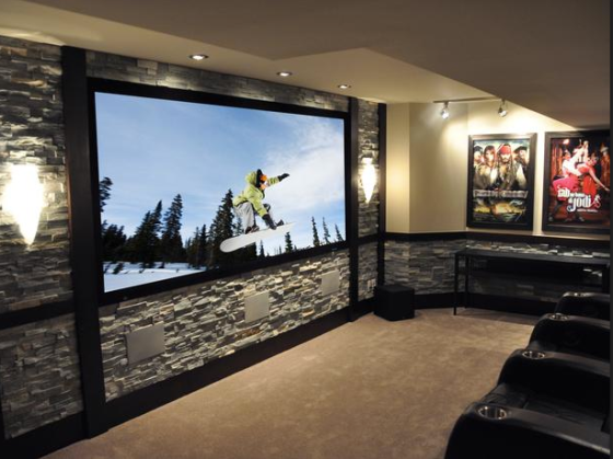 The dream - TV and speakers are incorporated into the wall (read: no cables hanging around), theatre-style seating and a nice touch of movie posters as decor. via HGTV.